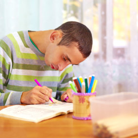 young man coloring a book
