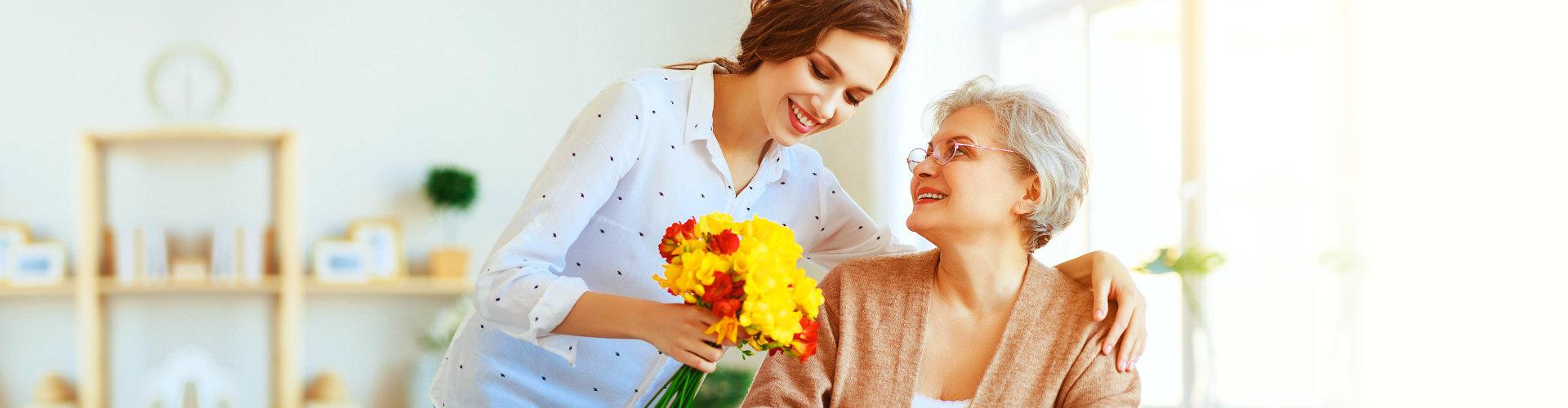 caregiver giving a senior woman flowers