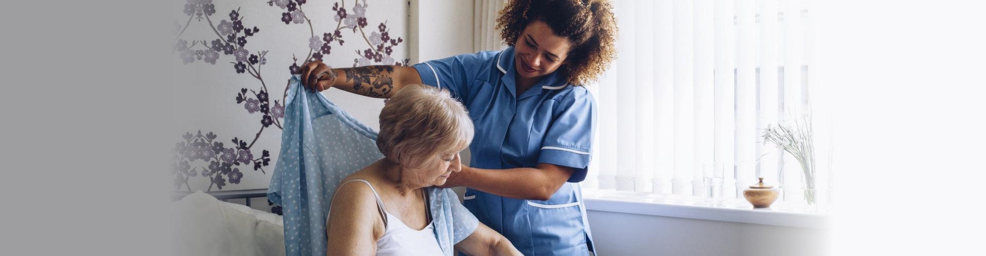 caregiver helping a senior woman get dressed